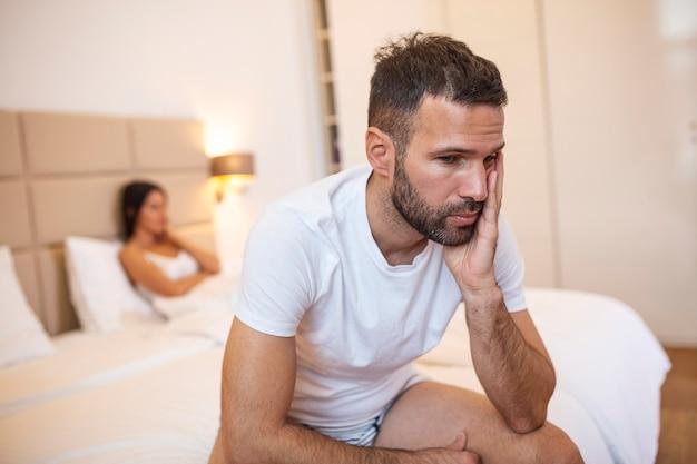 Mooi meisje en een gefrustreerde man die in bed zitten en niet naar elkaar kijken. Premium Foto