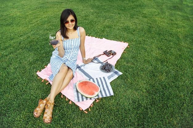 Mooi meisje geniet van wijn op een picknick. Premium Foto