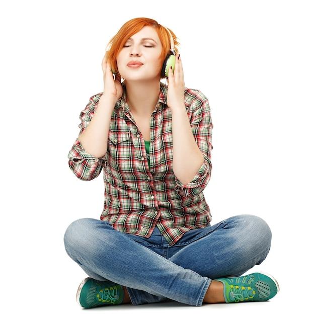 Mooi meisje genieten van het luisteren naar muziek op koptelefoon geïsoleerd op wit Premium Foto