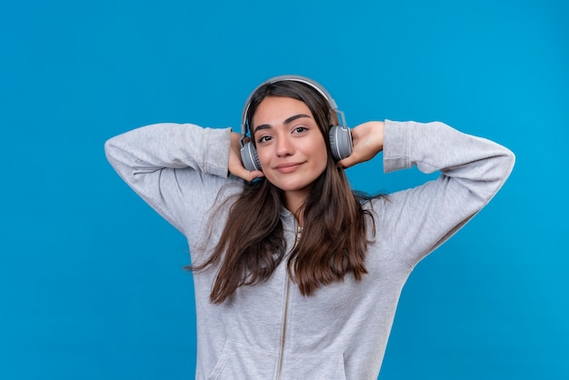 Mooi meisje grijze hoody camera kijken met een goed humeur en koptelefoon te houden die op oor staat over blauwe achtergrond Gratis Foto