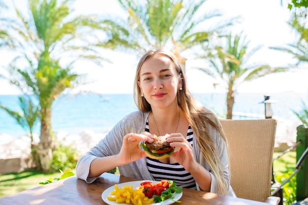 Mooi meisje heeft een hamburger op zee vakantie Premium Foto
