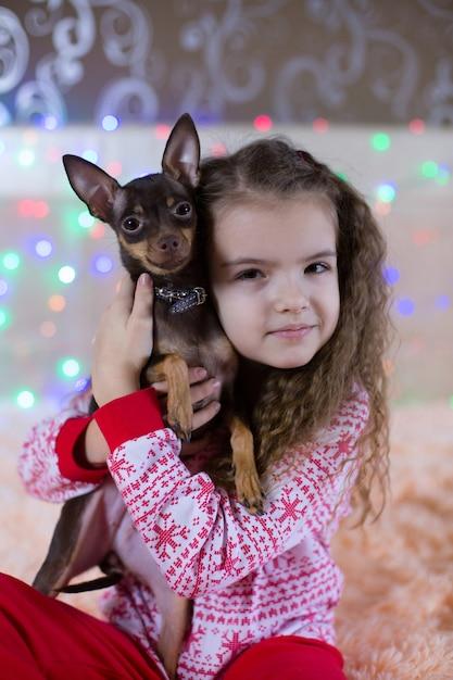 Mooi meisje in de pyjama van het nieuwe jaar. een kind knuffelt een stuk speelgoed terriërhond Premium Foto