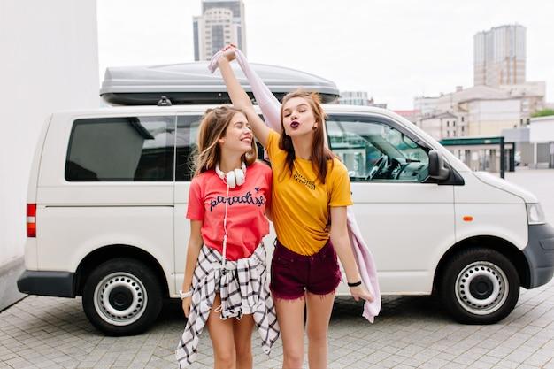 Mooi meisje in denim shorts met lichte make-up poseren met zoenen gezichtsuitdrukking terwijl haar vriend in roze shirt lachen Gratis Foto