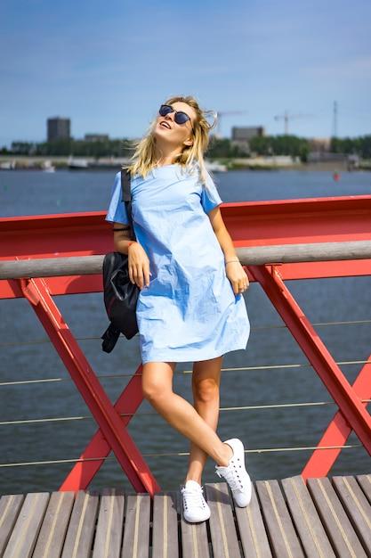 Mooi meisje in een blauwe jurk die zich voordeed op de brug Gratis Foto