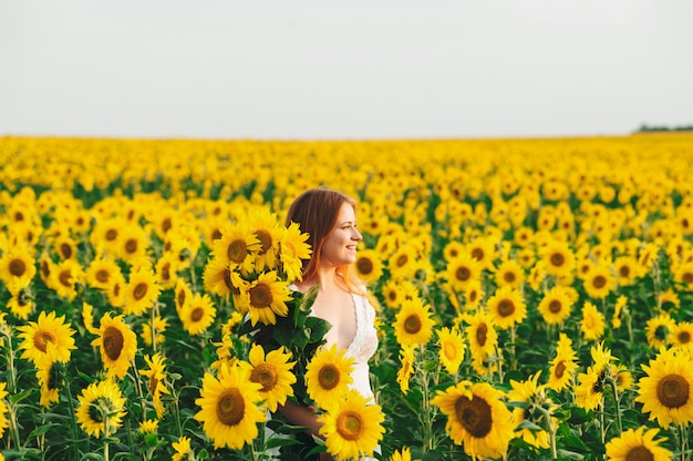 Mooi meisje in een enorm geel veld met zonnebloemen. Premium Foto
