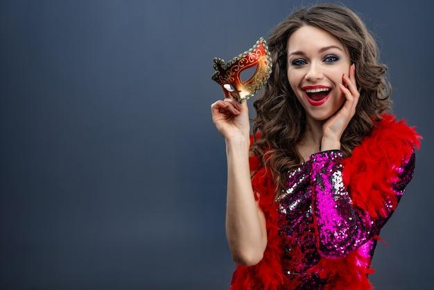 Mooi meisje in een glinsterende jurk en een boa om haar nek houdt een carnavalsmasker in verrukking Premium Foto