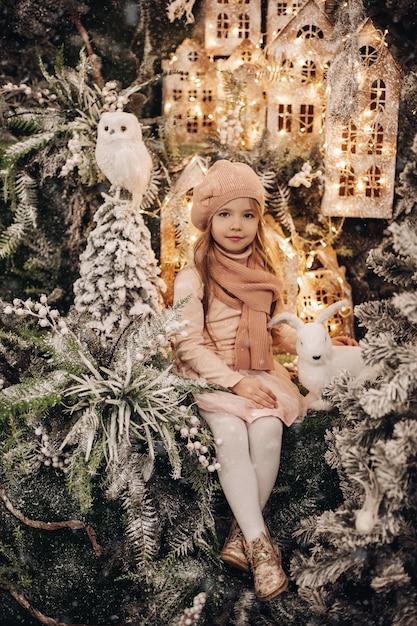 Mooi meisje in een kerstversiering met veel bomen onder een sneeuw en lichten Gratis Foto