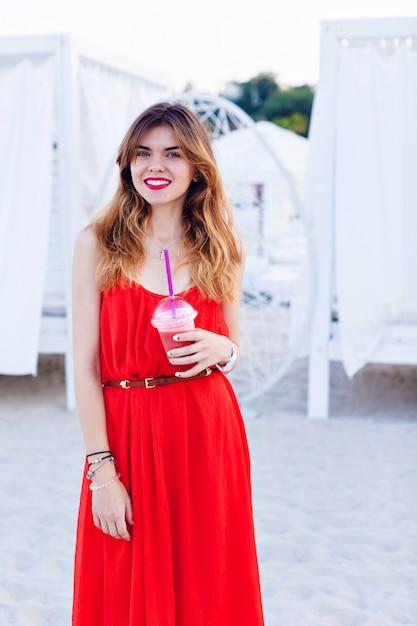 Mooi meisje in een rode jurk die zich op een strand bevindt en wijd lacht Gratis Foto