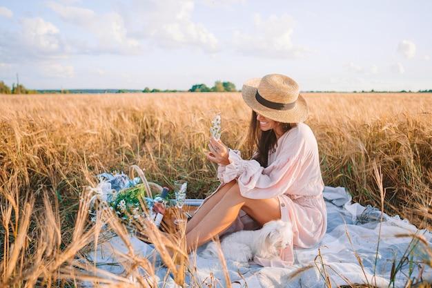 Mooi meisje in een tarweveld met rijpe tarwe in handen Premium Foto