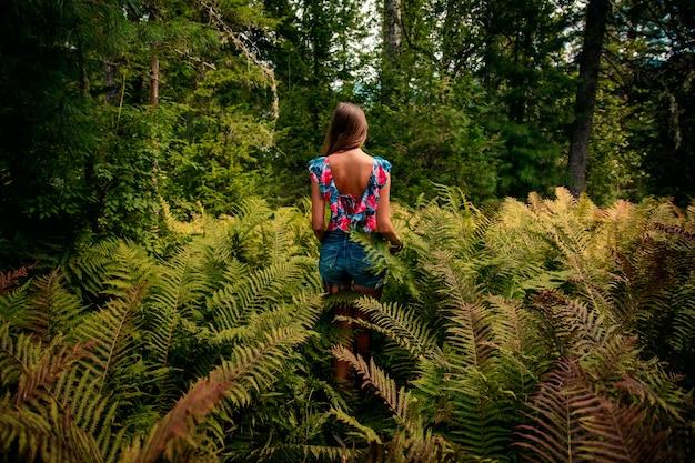 Mooi meisje in een varen in een zomer-bos Premium Foto