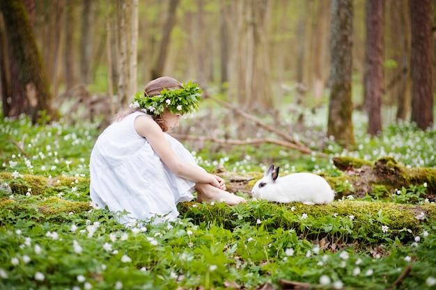 Mooi meisje in een witte jurk die met wit konijn in het de lentebos plaing Premium Foto