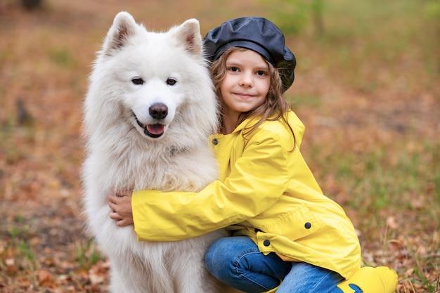 Mooi meisje in gele rubberen laarzen en regenjas op wandelingen, speelt met een mooie witte samojeed hond in het herfst park Premium Foto