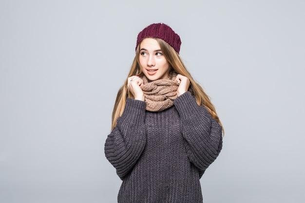Mooi meisje in grijze trui en sjaal is koud op grijs Gratis Foto