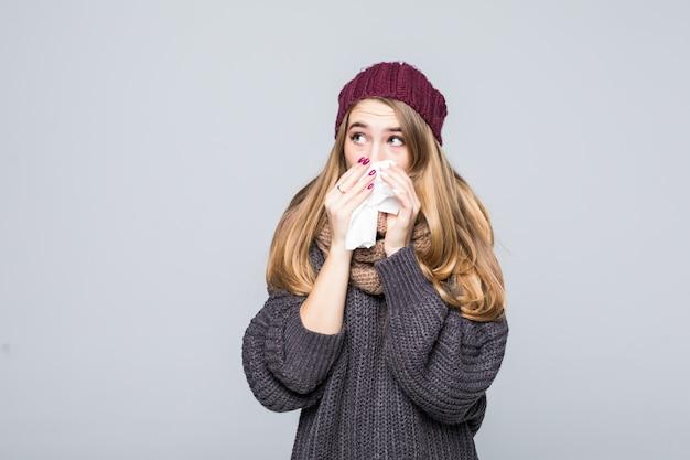 Mooi meisje in grijze trui heeft het koud en had griephoofdpijn op grijs Gratis Foto