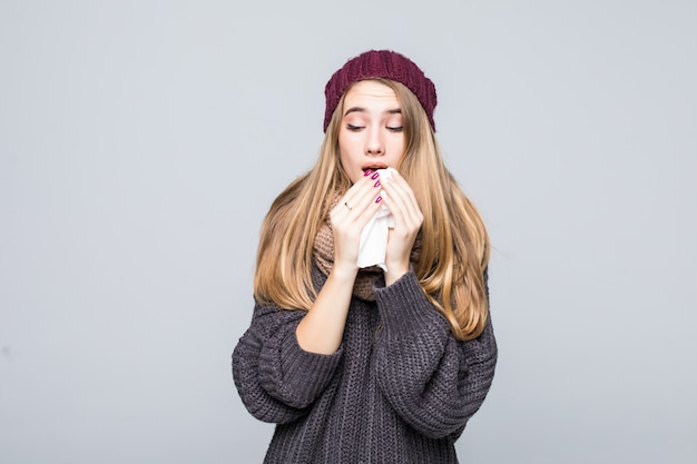 Mooi meisje in grijze trui is koud had griep niezen hoofdpijn op grijs Gratis Foto