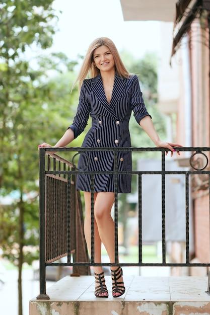 Mooi meisje in jas-jurk op balkon Premium Foto