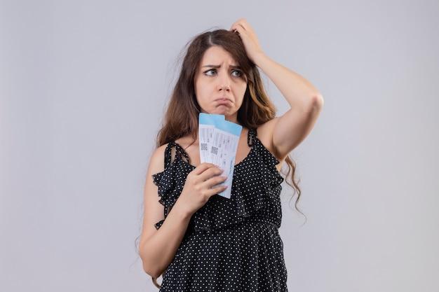 Mooi meisje in jurk in polka dot bedrijf vliegticket op zoek ontevreden met droevige uitdrukking op gezicht staande op witte achtergrond Gratis Foto