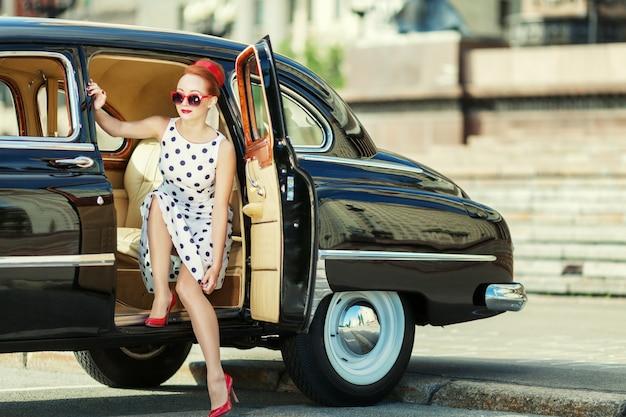 Mooi meisje in retro-stijl en een vintage auto Premium Foto