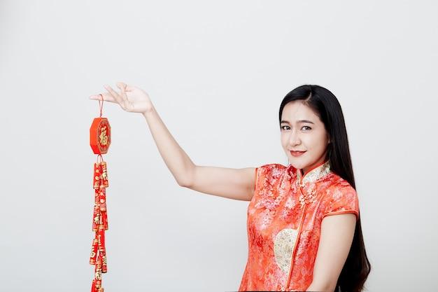 Mooi meisje in rode cheongsam die voetzoekers houden Premium Foto
