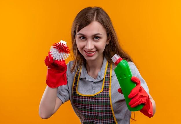 Mooi meisje in schort en rubberen handschoenen bedrijf schoonmaakproducten en schrobben borstel glimlachend vrolijk camera sluw te kijken Gratis Foto