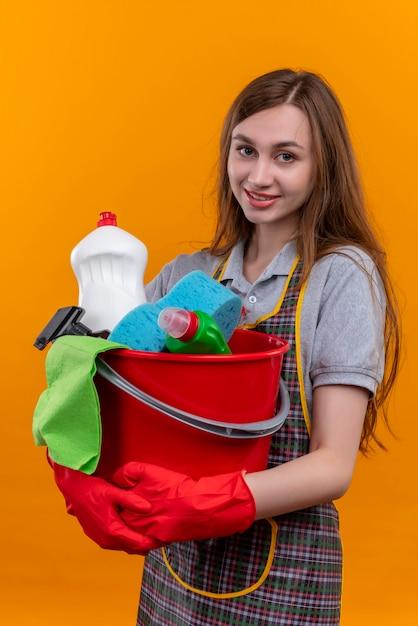 Mooi meisje in schort en rubberen handschoenen met emmer met schoonmaakgereedschap kijken camera glimlachend posotove en gelukkig Gratis Foto