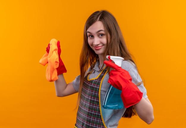 Mooi meisje in schort en rubberen handschoenen met schoonmaakspray en tapijt kijken camera glimlachend positief en gelukkig, klaar om te reinigen Gratis Foto