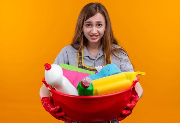 Mooi meisje in schort en rubberhandschoenen die bekken met het schoonmaken van hulpmiddelen houden die camera met sceptische glimlach op gezicht bekijken Gratis Foto