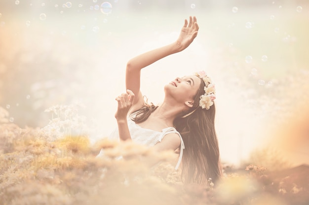 Mooi meisje in uitstekende kleding en hoed die zich dichtbij kleurrijke bloemen bevinden Premium Foto