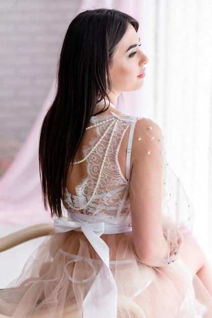 Mooi meisje in witte kanten boudoirjurk op de achtergrondkleuren decor met groot raam Premium Foto