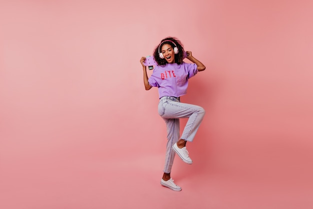 Mooi meisje in witte schoenen dansen in de studio terwijl u muziek luistert. portret van gemiddelde lengte van verfijnde afrikaanse dame met skateboard het koelen op roze. Gratis Foto