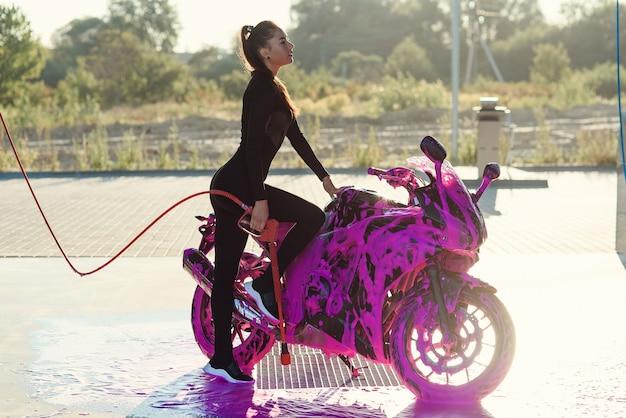 Mooi meisje in zwart verleidelijk pak staat in de buurt van motorfiets bij self-carwash bij zonsopgang. Premium Foto