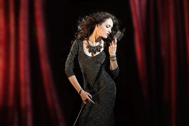 Mooi meisje in zwarte jurk zingen in de microfoon in het concertgebouw Premium Foto