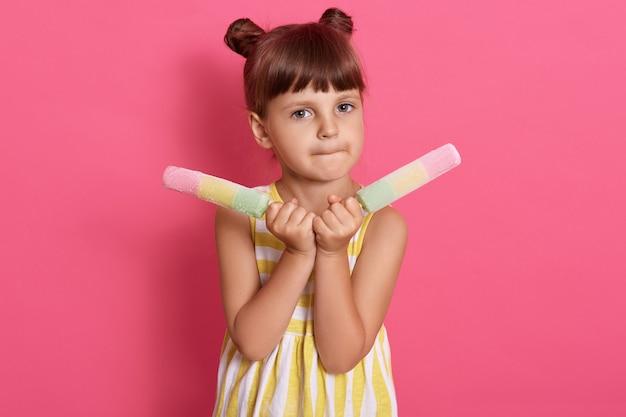Mooi meisje kind eten met twee grote ijs, het dragen van witte en gele jurk, met twee haren broodjes, poseren tegen roze muur met twee sorbets. Gratis Foto