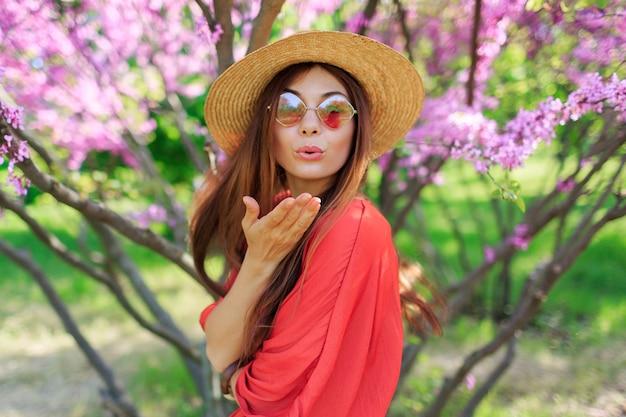 Mooi meisje lucht kus verzenden naar camera in zonnige lentedag. roze bloeiende bomen o Gratis Foto