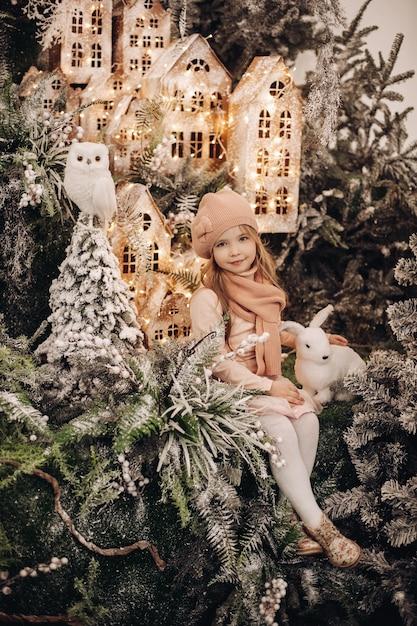 Mooi meisje maakt foto's in een kerstversiering met veel bomen onder een sneeuw en lichten Gratis Foto