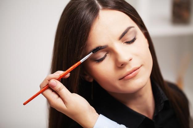Mooi meisje maakt gebruik van de diensten van een professionele visagist in een schoonheidssalon Premium Foto