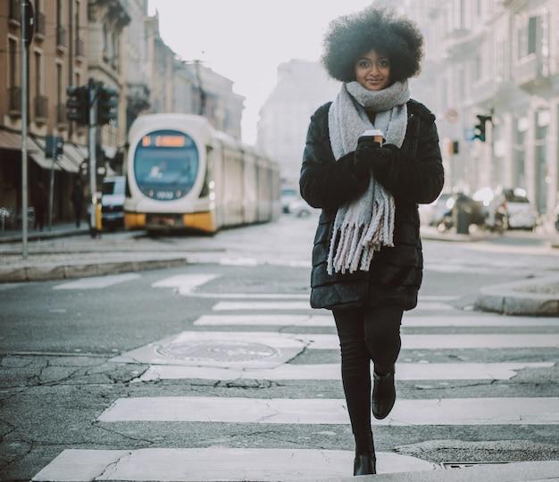 Mooi meisje met afro kapsel lopen op straat Premium Foto