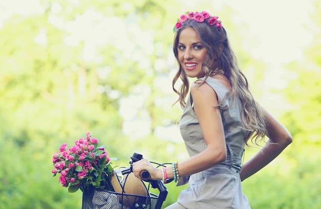 Mooi meisje met bloemen op een fiets Gratis Foto