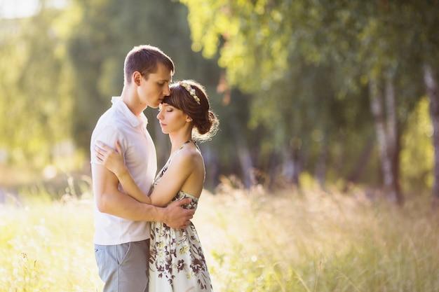 Mooi meisje met donker haar en bruine ogen met een krans op hoofd in zomerjurk knuffelen een man in een wit overhemd op een groene achtergrond. verliefde paar in het bos op een zonnige dag. van elkaar houden Premium Foto