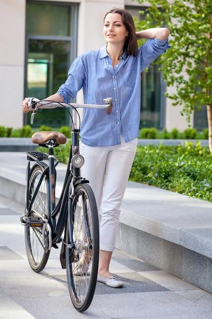 Mooi meisje met een fiets op de weg Gratis Foto