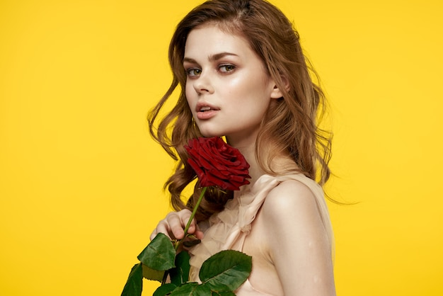 Mooi meisje met engelachtige verschijning met een roze bloem in haar handen Premium Foto