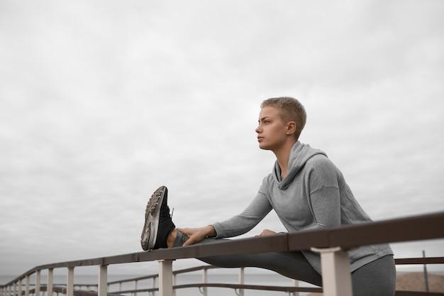 Mooi meisje met fit lichaam uitrekkende been met behulp van rail op strand, spieren voorbereiden op cardiotraining, zelfverzekerd zelf bepaald look. mensen, activiteit, gezondheid, fitness en sportconcept Gratis Foto