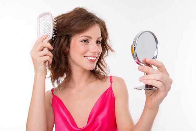 Mooi meisje met golvend bruin haar, schone huid, platte tanden, mooie glimlach, in roze trui, met een berekening en spiegel berekent haar haar en glimlacht Premium Foto