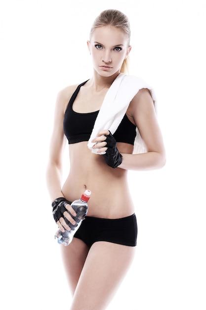 Mooi meisje met handdoek en fles water Gratis Foto