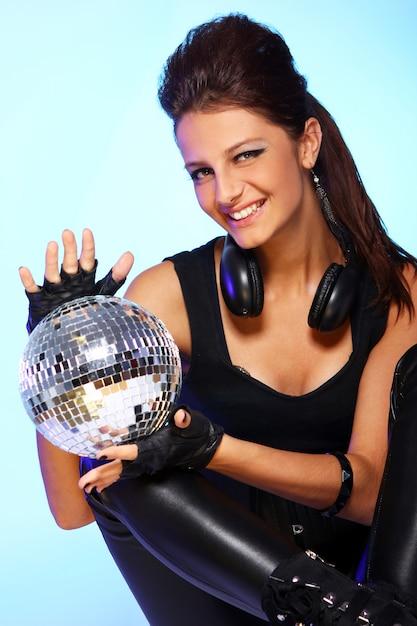 Mooi meisje met hoofdtelefoons en discobal Gratis Foto