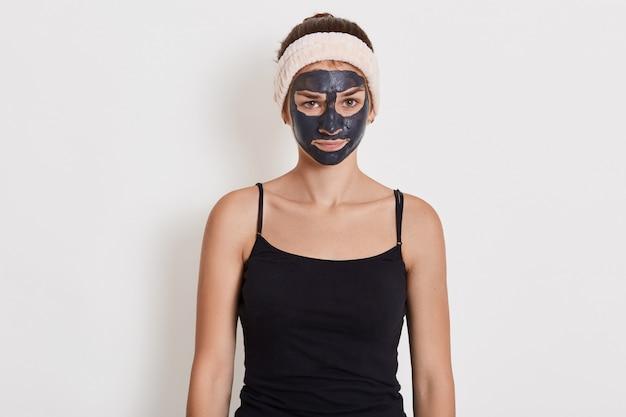 Mooi meisje met kleimasker op haar gezicht dat zich met verstoorde gelaatsuitdrukking met droefheid bevindt, die zwarte t-shirt en haarband draagt. Gratis Foto