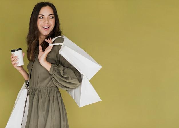 Mooi meisje met koffie en veel winkelnetten terugkijkend Gratis Foto