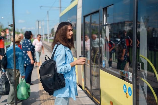Mooi meisje met kopje koffie komt in de moderne tram op het station. Premium Foto