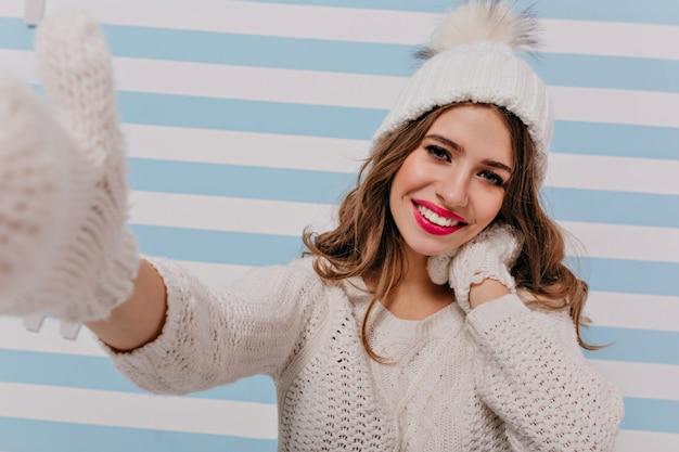 Mooi meisje met lang haar maakt gelukkig selfie. europees model in winter gebreide outfit leuke poses Gratis Foto