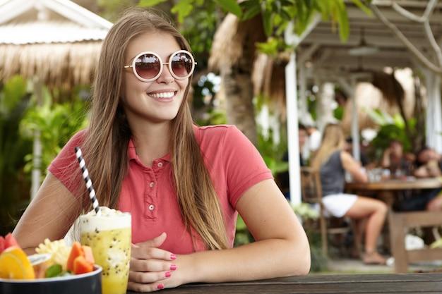 Mooi meisje met lang haar ontbijten op terras op strand tijdens vakanties in exotisch land. Gratis Foto